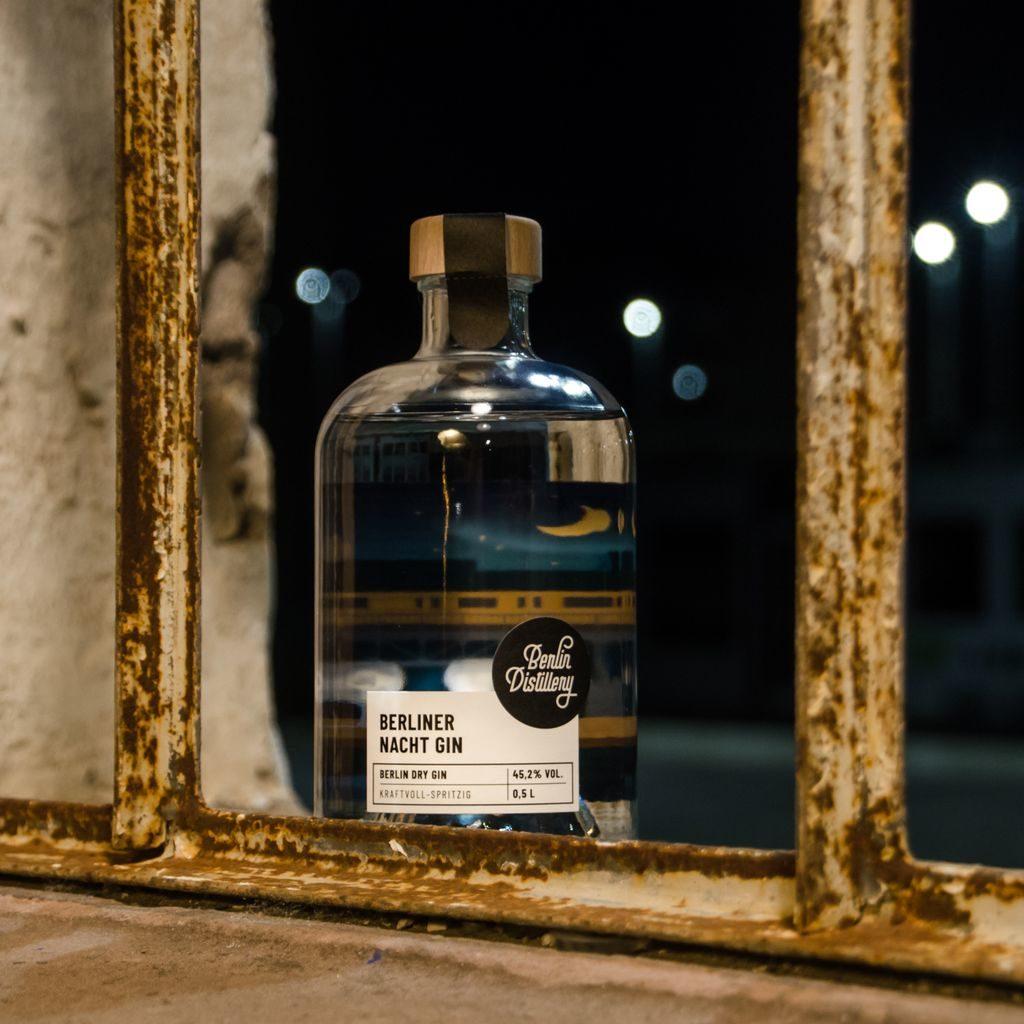 Berlin Distillery Berliner Nacht Gin bei Nacht zwischen zwei Stangen eines Geländers