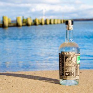 Eine Flasche des Freytag Concrete Jungle Gin vor einem Fluss