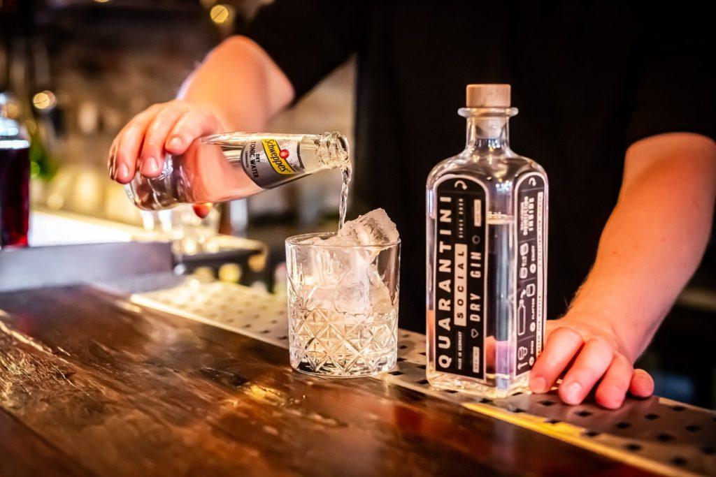 Flasche Quarantini Social Dry Gin in der Bar als Gin Tonic